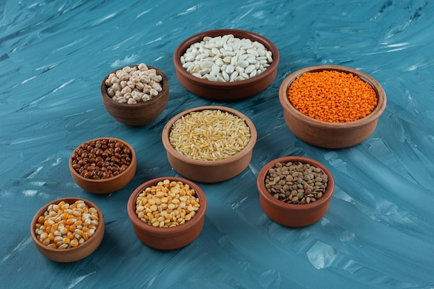 Various types of beans, cereals, corns and lentils placed in bowls.