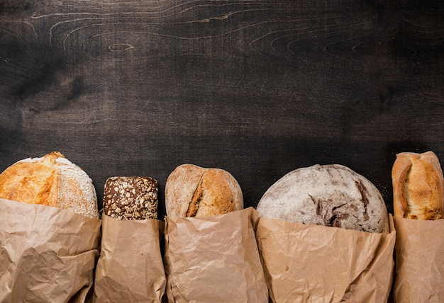 Various types of bread wrapped in paper and copy space