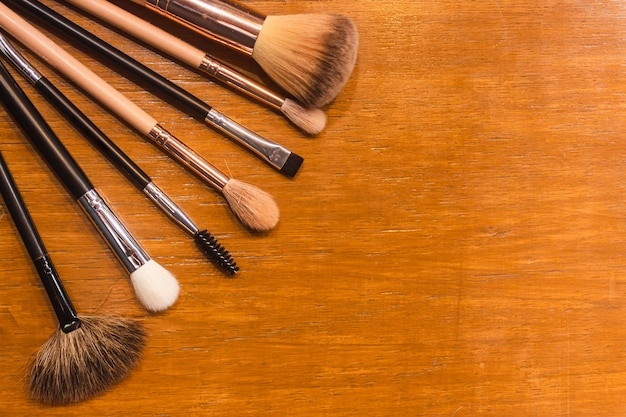 Various types of brushes and other makeup accessories on a wooden table.