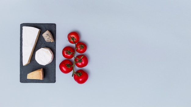 Various types of cheese on black slate with red tomatoes over grey surface with copy space