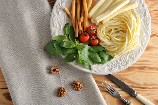 Various types of cheese in a bowl with basil and cherry tomatoes with cheese chechil, straws, smoked cheese