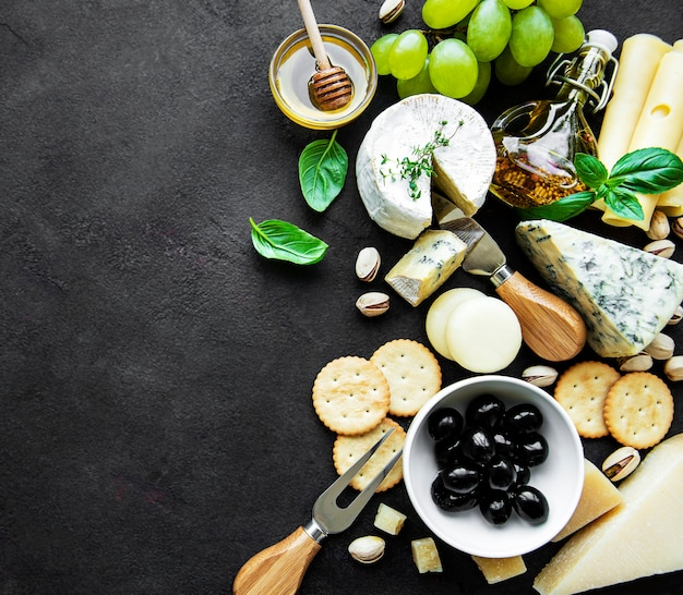Various types of cheese, grapes, honey and snacks on a black concrete surface