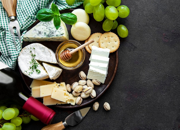 Various types of cheese, grapes and wine on a black concrete background