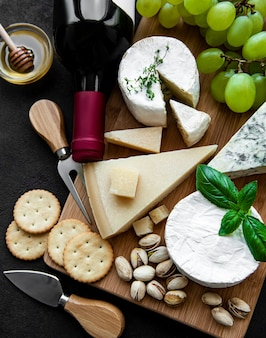 Various types of cheese, grapes and wine on a black concrete surface