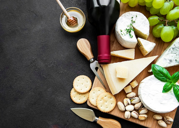 Various types of cheese, grapes and wine on a black