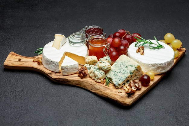 Various types of cheese and jam on wooden cutting board