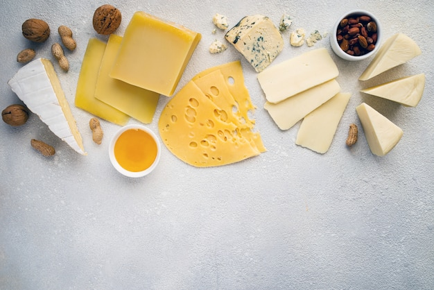 Various types of cheese on a white table. top view