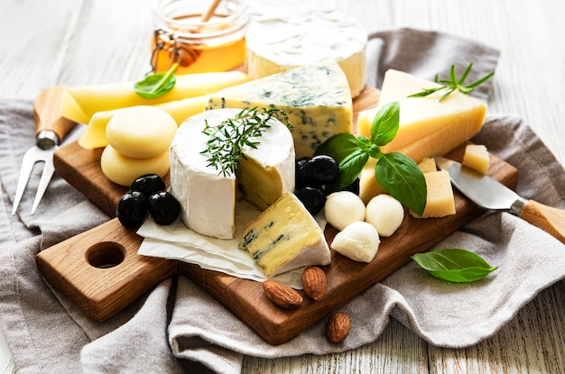 Various types of cheese  on a white wooden  surface