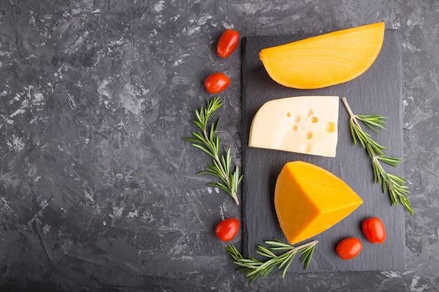 Various types of cheese with rosemary and tomatoes on black slate board on a black concrete background. top view, copy space.