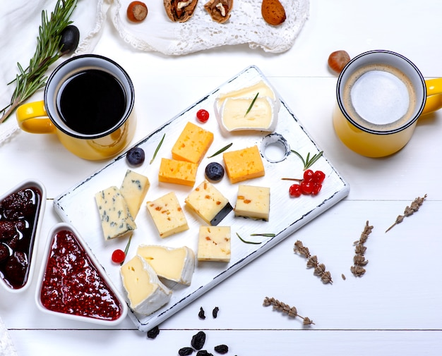 Various types of cheese with tartar and clove jam and black coffee