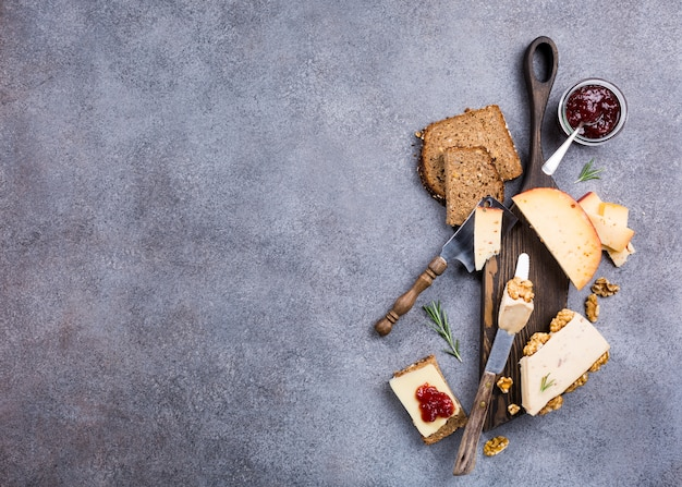 Various types of cheese with whole grain bread, strawberry jam and walnuts on wooden board