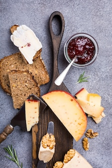 Various types of cheese with whole grain bread, strawberry jam and walnuts