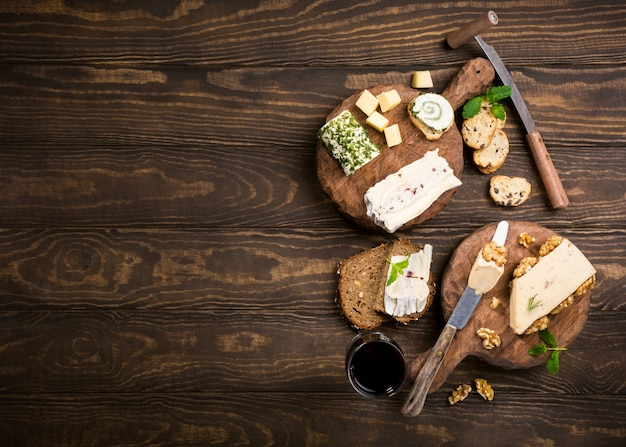 Various types of cheese with wholegrain bread, crackers and wine on wooden boards.