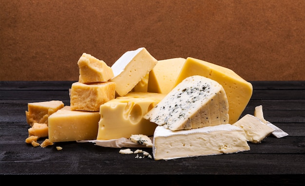 Various types of cheese on wooden surface table