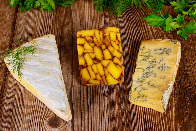 Various types of cheese on wooden surface