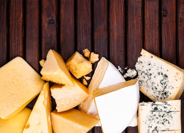 Various types of cheese on wooden table, top view