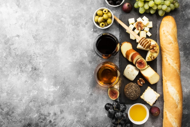 Various types of cheeses, figs, nuts, honey, grapes, bread