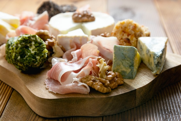 Various types of cheeses, grapes, walnuts and honey and prosciutto.