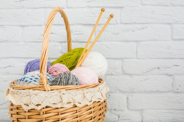 Various types of colorful wools in wicker basket