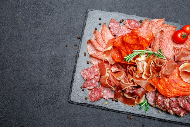 Various types of dried organic salami sausage and parma on concrete background