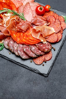 Various types of dried organic salami sausage and parma on concrete surface