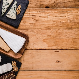 Various types of fresh cheese pieces on wooden plate and stone tray over wooden backdrop