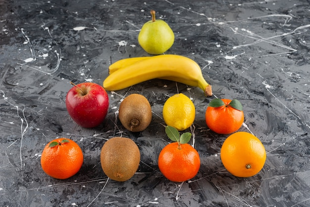 Various types of fresh juicy fruits placed on marble table .