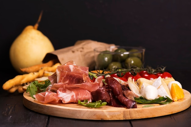 Various types of italian appetizers: ham, cheese, grissini, olives, fruits