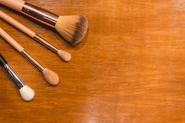 Various types of makeup brushes on a wooden table.