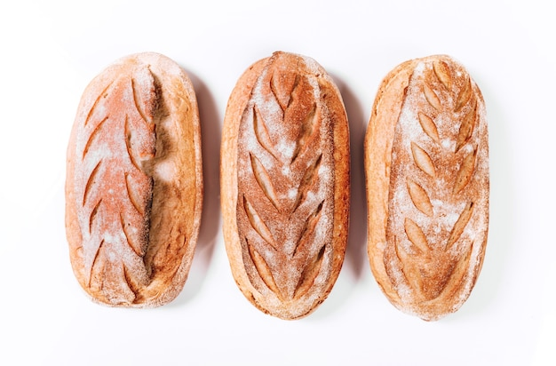 Различные виды хлебобулочных изделий - свежие деревенские хрустящие буханки хлеба и багет на белом фоне.