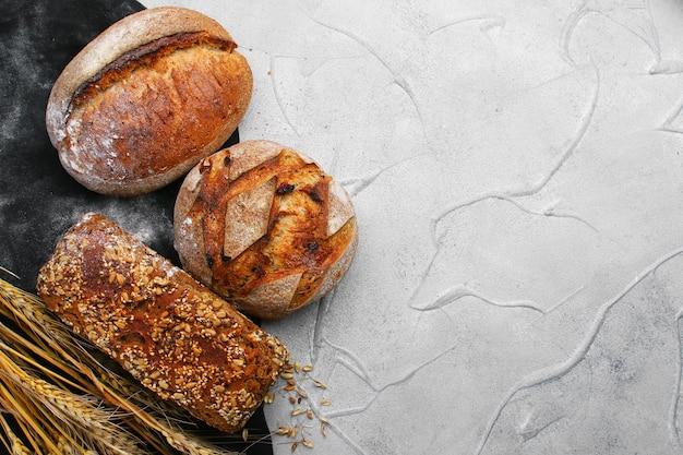 Различные виды хлеба на вид сверху бетонного стола.