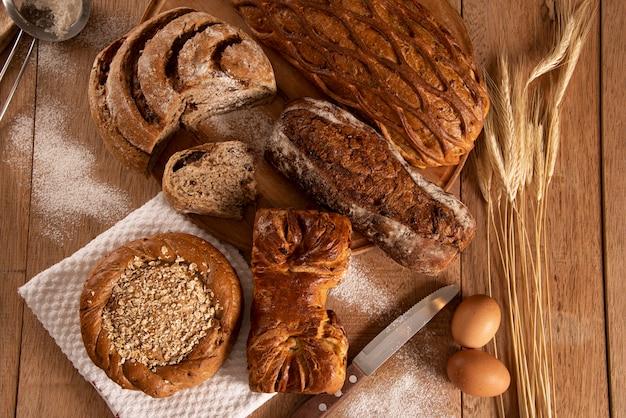 Различные виды хлеба на деревянном столе с деревенским фоном