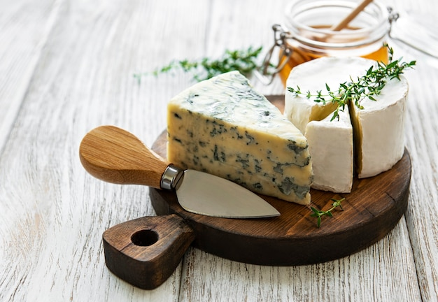 木製のテーブルにさまざまな種類のチーズ、ブルーチーズ、ブリー、カマンベール、蜂蜜