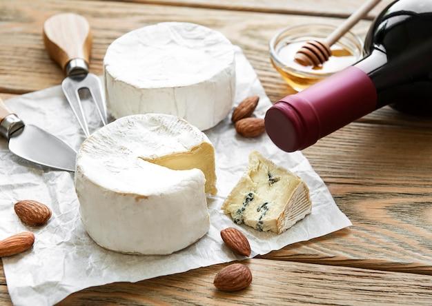 木製のテーブルにさまざまな種類のチーズ、ブルーチーズ、ブリー、カマンベール、ワイン
