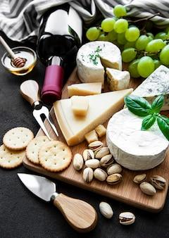 Различные виды сыра, винограда и вина на черной бетонной поверхности