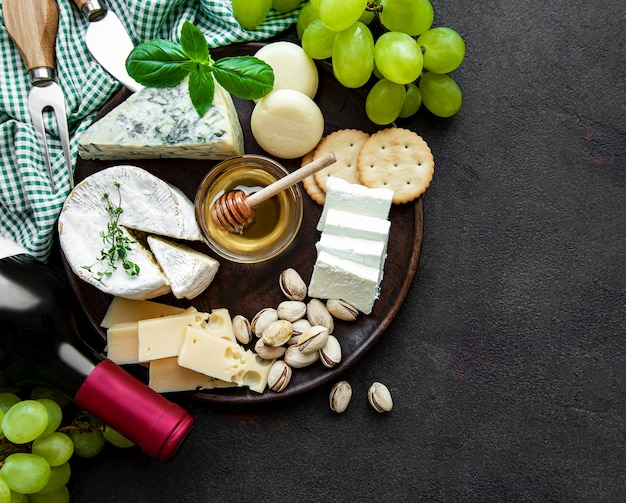 Различные виды сыра, винограда и вина на черном бетонном столе