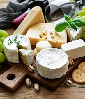 木製のテーブルにさまざまな種類のチーズ、ブドウ、ワイン