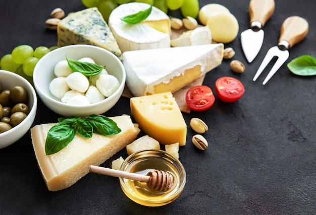 Различные виды сыра, винограда, меда и закусок на черной бетонной поверхности