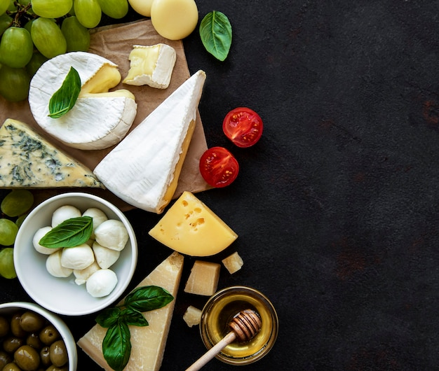 검은 콘크리트 표면에 다양한 종류의 치즈, 포도, 꿀, 스낵