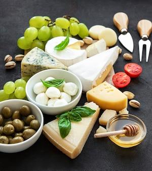Различные виды сыра, винограда, меда и закусок.