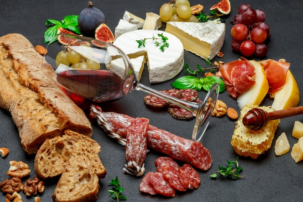 Различные виды сыра, мяса, фруктов и вина