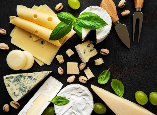 黒いコンクリートの表面にさまざまな種類のチーズ