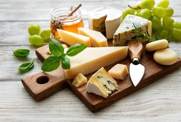Различные виды сыра на белом деревянном фоне