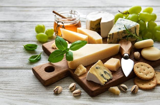 白い木の表面にさまざまな種類のチーズ