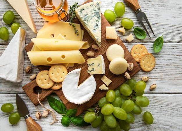 白い木製のテーブルにさまざまな種類のチーズ