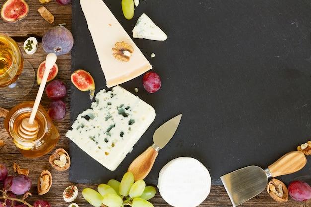 コピースペースのある黒いまな板にさまざまな種類のチーズ