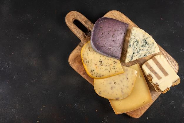 어두운 배경에 다양한 종류의 독점 치즈.