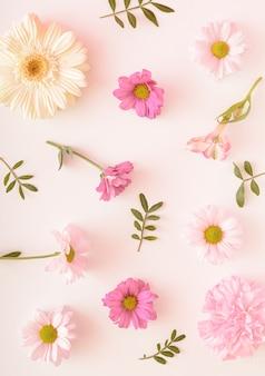 Различные виды цветов нежных расцветок на светлом фоне. хризантемы, гвоздики, герберы, спонтанно расположенные в виде узора. летняя весенняя цветочная концепция.