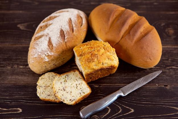 暗い木製の背景に焼きたてのパンの様々な種類