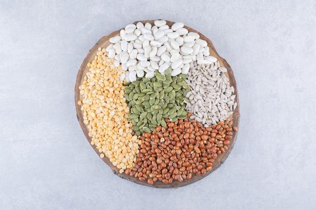 大理石の表面の丸太のスライス上のさまざまな種類の穀物、種子、マメ科植物